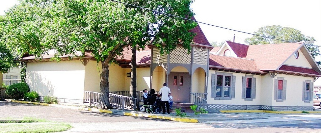 View of VAIL-ST Office showing building with entryway and 3 people, one in a wheelchair.